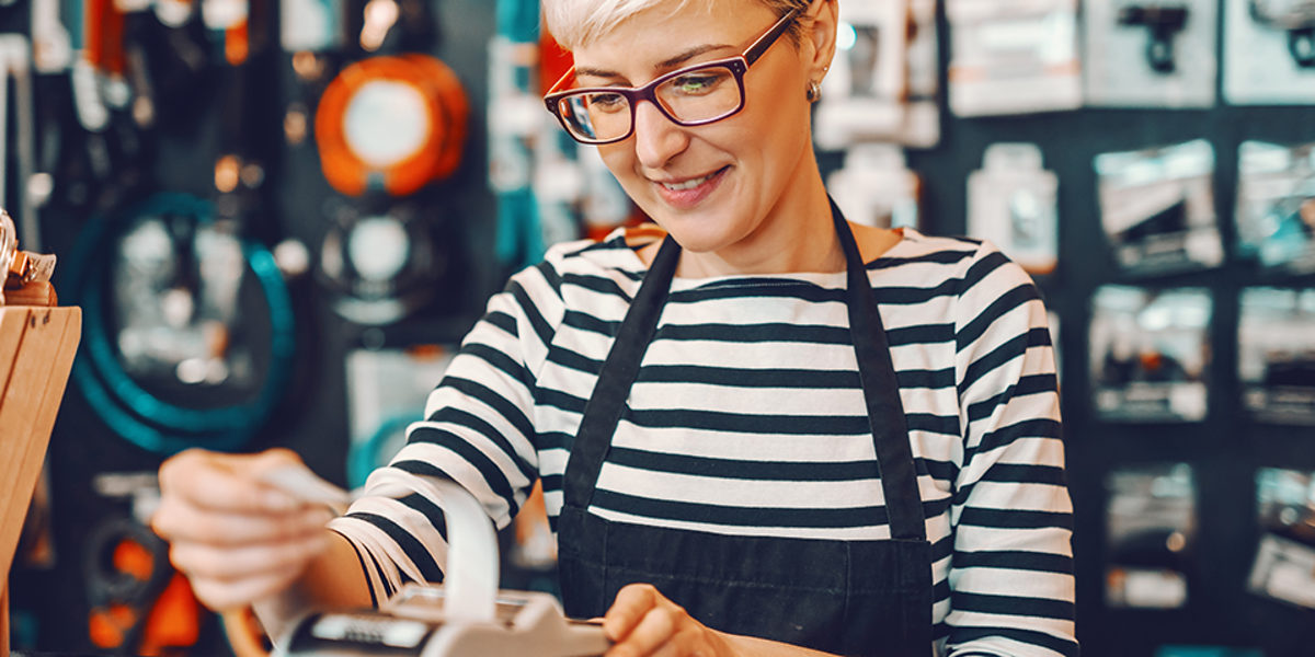 Smiling Caucasian female worker with short blonde hair and eyeglasses using cash register while standing in bicycle store. Schlagwort(e): counter, cashier, woman, retail, press, payment, cash counter, cashier machine, store, seller, consumerism, bill, payment terminal, paying, register, cash, sales person, saleswoman, staff, cash register, indoors, financial, contemporary, worker, employee, equipment, check out, job, commercial, beautiful, billing counter, cashier counter, cashier desk, purchase, finance, sale, bicycle, workplace, cyclist, owner, profession, son, selling, city-bike, gear, alternative, bike, working, smiling, shop